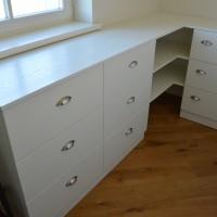 Baltas kampinis stalas su stalčiais ir lentynom