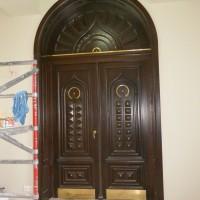 Rudos dviejų dalų medinės durys suapvalintu viršum ir aukso spalvos detaliu akcentais