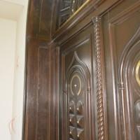 Rudos medinės durys suapvalintu viršum ir aukso spalvos detaliu akcentais