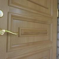 Medinės durys su aukso spalvos rankena